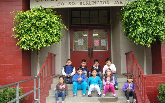 Kids sitting in front of school sign